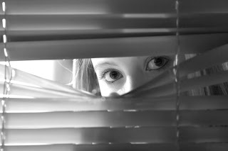 Illustration of young woman looking nervously through blinds.