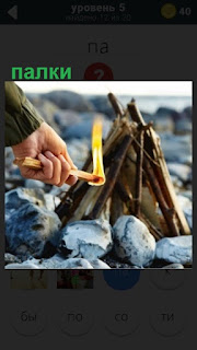 небольшой костер из палок поджигают лучиной на берегу