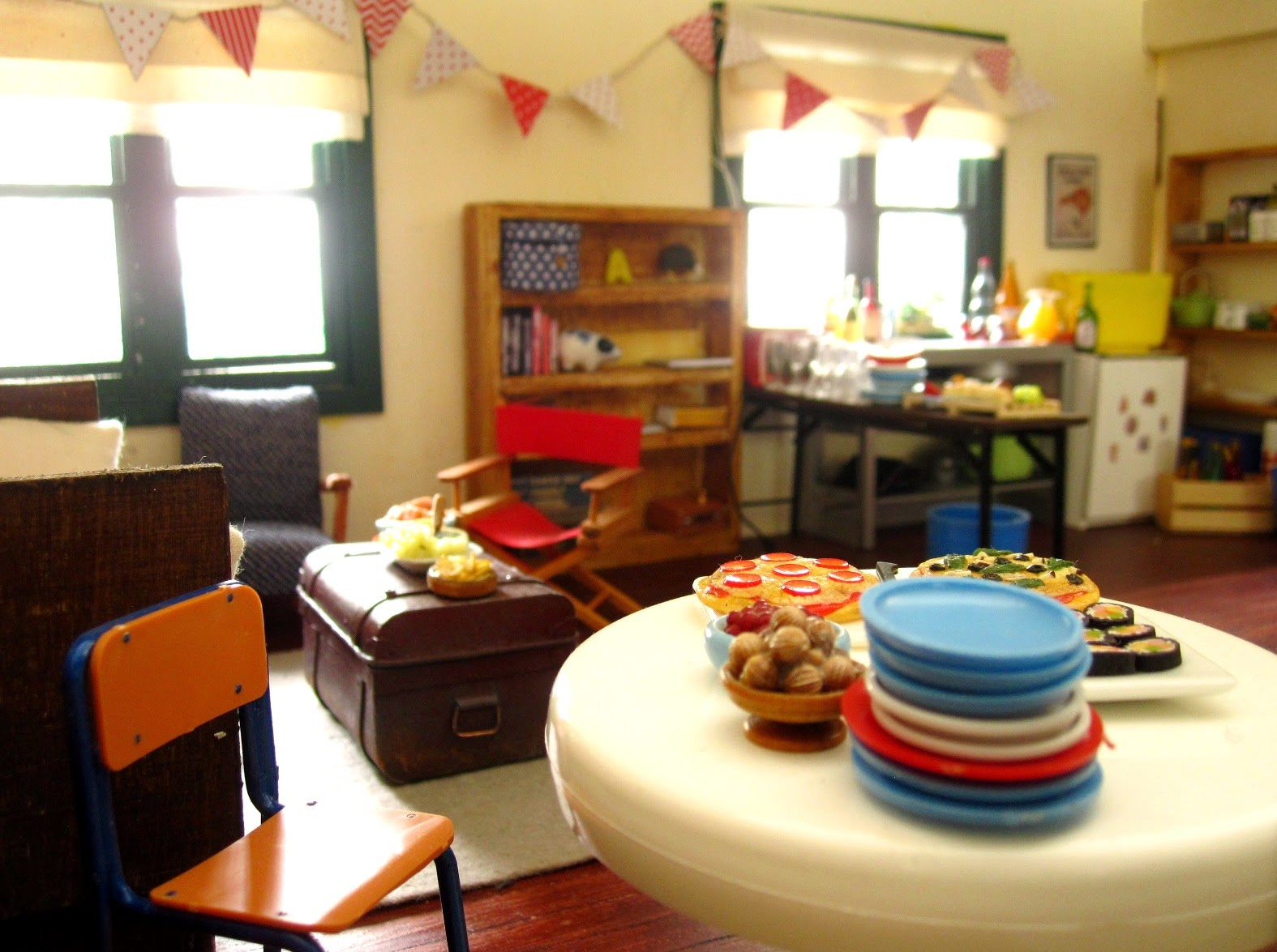 A miniature dolls' house living room, set up for a party with food, seating and plates arranged.