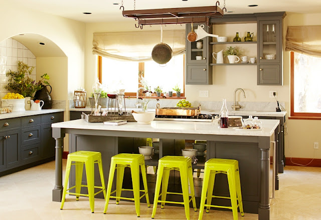 kitchen with gray cabinets, island with marble counter top, chartreuse stools and hanging pot rack