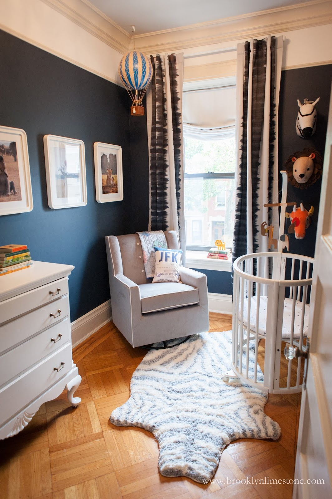 Safari nursery with grey chair, white crib and animal print rug