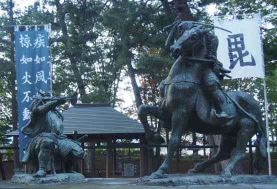 床几に腰掛ける武田信玄と馬上から斬りかかる上杉謙信の像