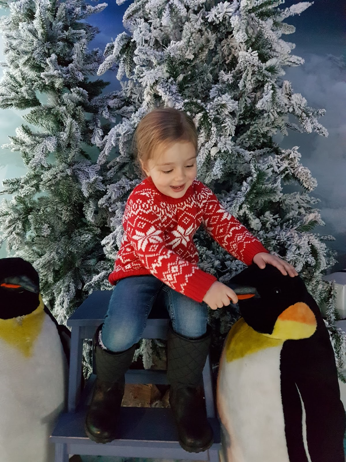 girl sitting with penguins at harrods christmas grotto