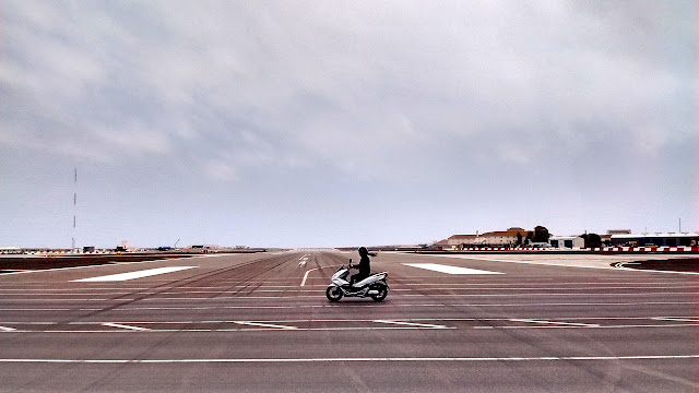 Photo of a motorcycle crossing the runway of the Gibraltar airport. The road crossing the runway is the only land route in or out of the British territory which borders Spain.