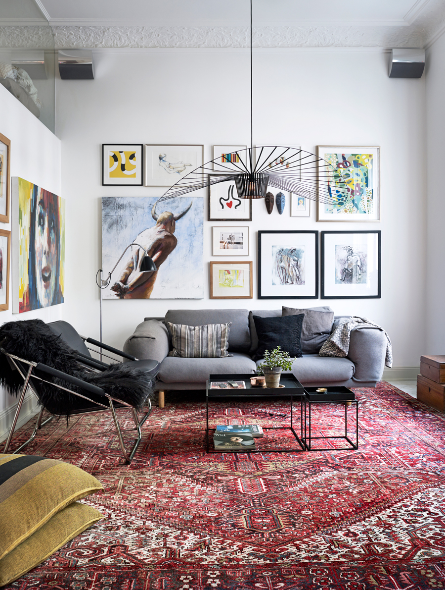 persian rug, gallery wall and gray sofa in Scandinavian apartment