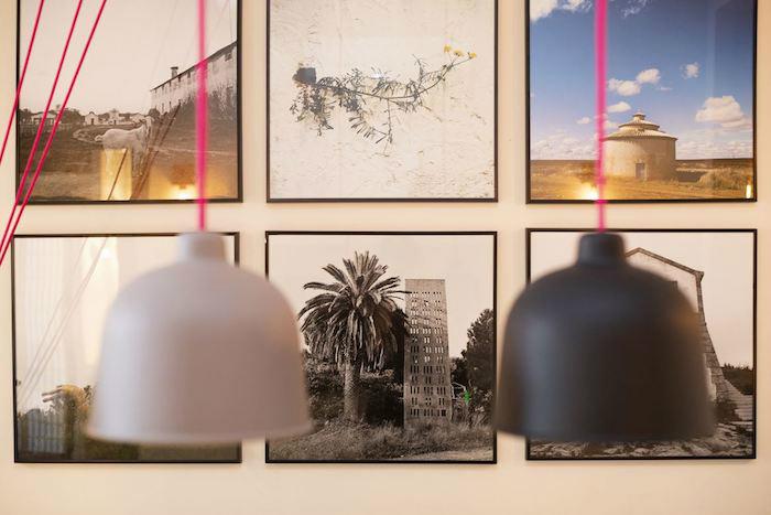 Cómo decorar un apartamento joven con poco dinero: colección de cuadros en la pared con marcos negros, y lámparas con cables en rosa neón.