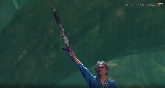 The Game Awards 2017 Eiji Aonuma holding Master Sword out of pedestal above head rusted