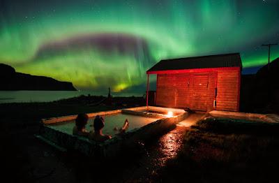 Pareja relajandose con la Aurora de fondo en Islandia