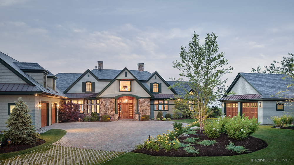 Exterior of an elegant oceanview home lit up at dusk in coastal Maine and built by Bowley Builders.