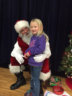 Young girl in purple hoodie and jeans standing with Santa Clause