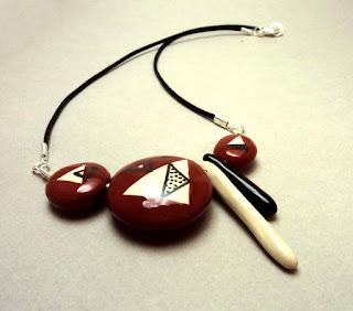 collier de créateur avec galets de céramique rouge à graphismes noir et blanc