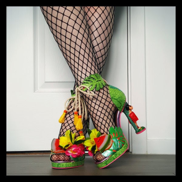 crossed legs wearing fishnet tights and leaf and flower and fruit covered shoes