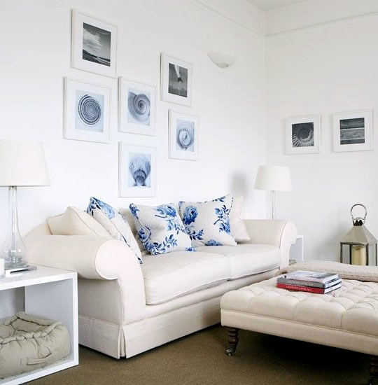 Simple airy coastal living room with shell art gallery wall above sofa