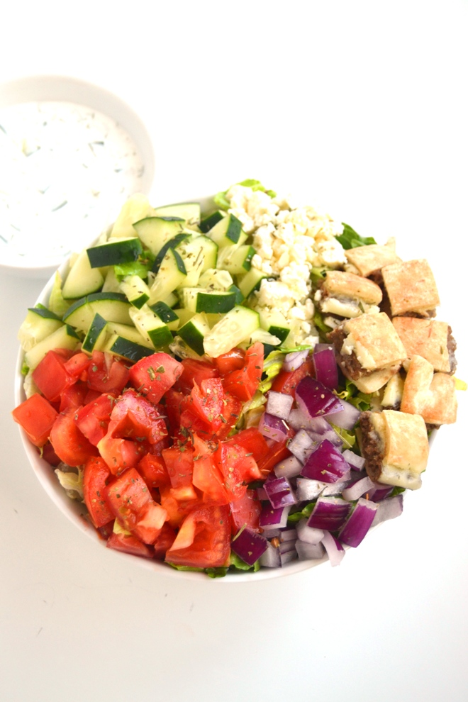 Gyro Salad with Tzatziki takes just 10 minutes to make and is loaded with tomatoes, cucumber, gyro sliders, red onion, feta cheese and is topped with homemade tzatziki sauce. www.nutritionistreviews.com
