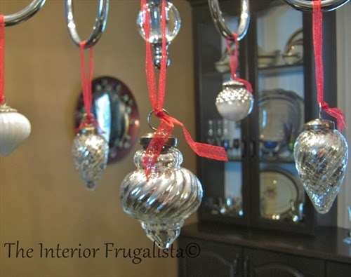 Mercury glass balls hanging by ribbon on the chandelier