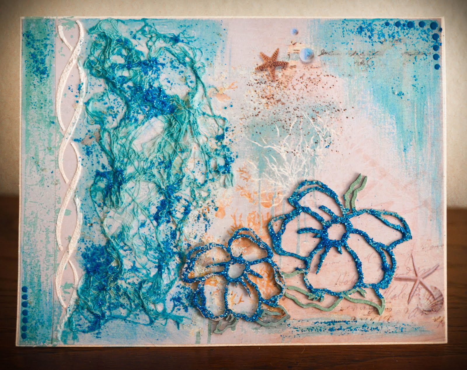 Mixed media card with stenciling, glitter, and chipboard flowers in aqua blue and beige