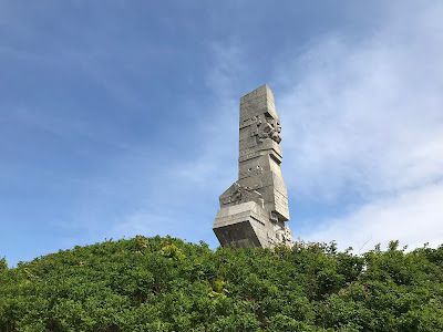 westerplatte monument with trees in the foreground and a blue sky behind