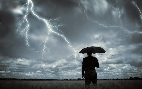 Homem de preto com guarda-chuva em uma tempestade com relâmpagos