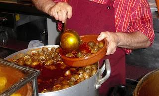 Momento en que el camarero sirven una ración de caracoles en la típica cazuelita de barro.