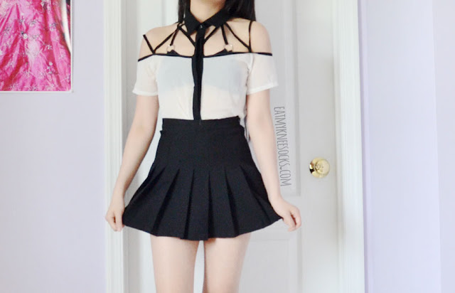 A monochrome black-and-white outfit featuring an off-shoulder caged cutout blouse shirt from Dresslink, paired with an American Apparel style pleated tennis skirt and UNIF Salem strappy bra dupe.