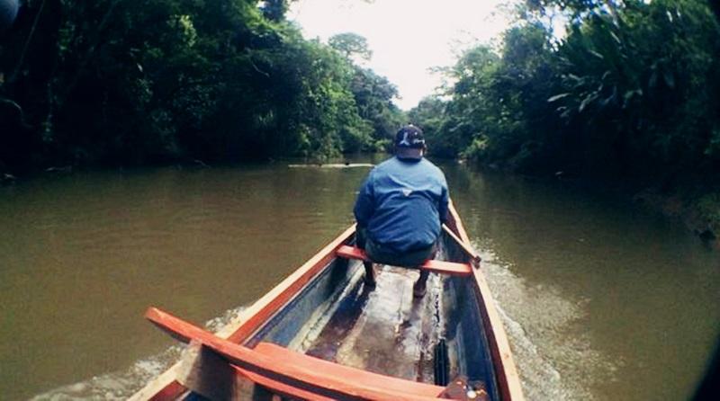 Homem navegando na proa da canoa pelo rio