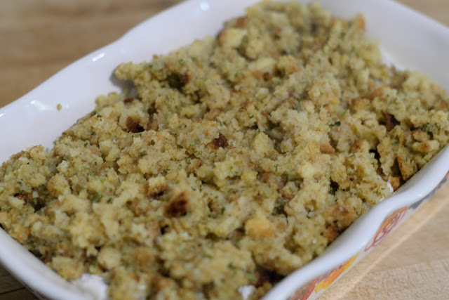 The cooked stuffing sprinkled over chicken and cream mixture in the casserole dish.