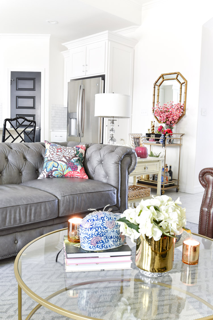 A white living room with a gray chesterfield sofa paired with a gold bar cart and coffee table. Love this open concept space. #whitewalls #alabaster #livingroom #barcart
