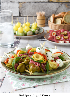 Gemarineerde mozzarella, zelfgemaakte geroosterde paprika, tortellini, basilicum, salami, zelfgemaakte zuur komkommer en gemarineerde olijven met paprika