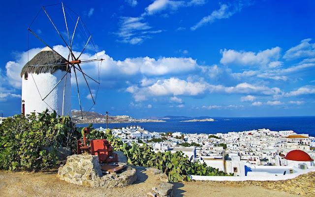 Molen ergens in Griekenland met een stad en de zee op de achtergrond