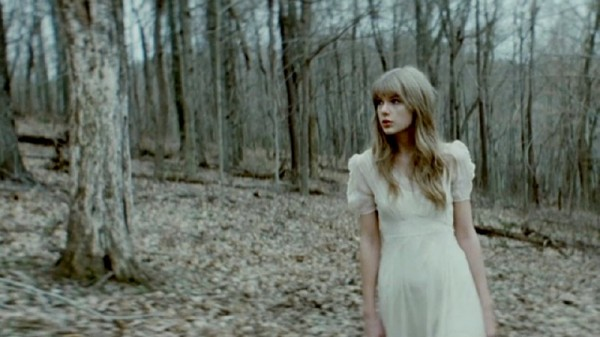 Taylor Swift walks through a wooded area