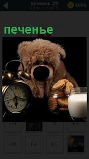Игрушка медведя, будильник и печенье со стаканом молока на столе