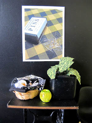 Detail of a modern dolls' house miniature scene of a vintage sewing table and Eames chair in front of a black wall displaying a poster with vintage pins on a checked fabric.