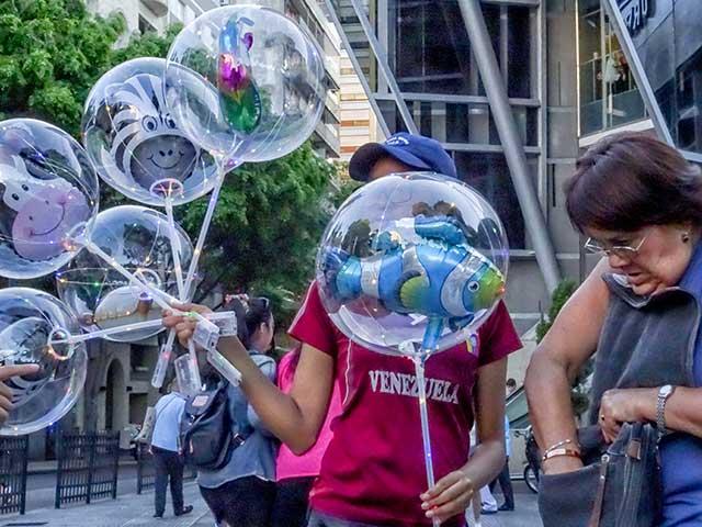 Vendedora ambulante de globos transparente con muñecos en el interior.
