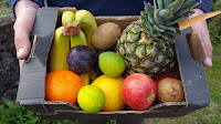 A large box of fruit with banana, apple, orange, lemon, lime, kiwi, plum and pineapple