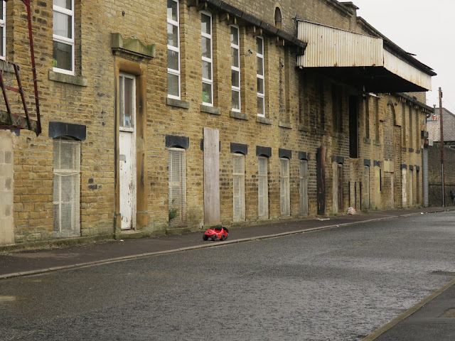 Child's pedal car left on tarmac pavement beside crumbling mill in side-street. Halifax UK