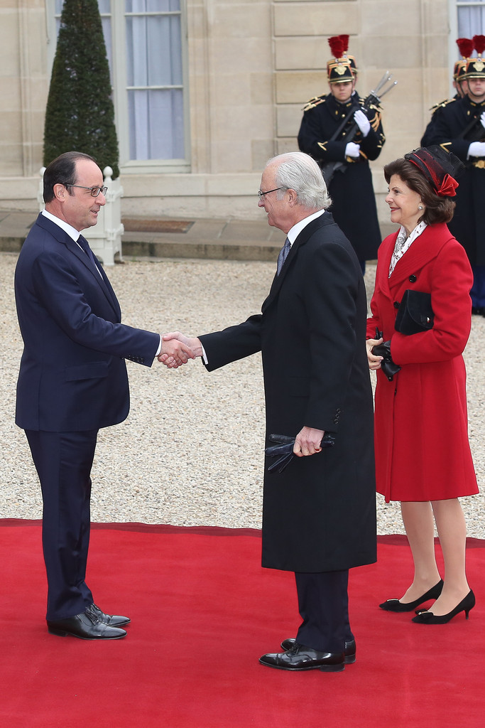French President Francois Hollande (C) delivers a speech as Swedish King Carl XVI Gustaf (L) and Queen Silvia (R) listen during a state dinner at the Elysee presidential palace in Paris