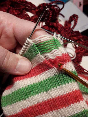 A hand knit sock in red, white and green stripes, with a very wide ladder down one side.  At the bottom of the ladder is a crochet hook, holding one stitch.  The ladder is wider than the one stitch on the crochet hook.