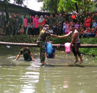 Personel Yon Zipur dan Polsek Helvetia yang bertanding adu pukul pakai bantal di atas kolam.