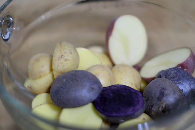 The raw potatoes, cut in half, in a glass mixing bowl.