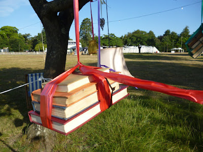 Books hanging from a tree by ribbon curious arts festival