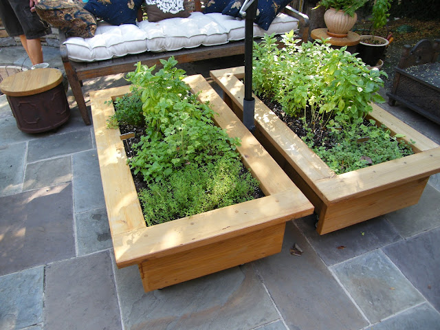 Wood raised bed planters fit right in with furniture and guests on the slate patio.