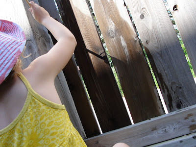 using water to paint a fence with child