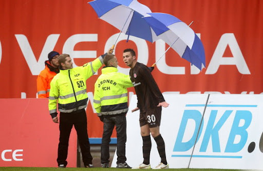 St Pauli player takes corner with umbrella protection