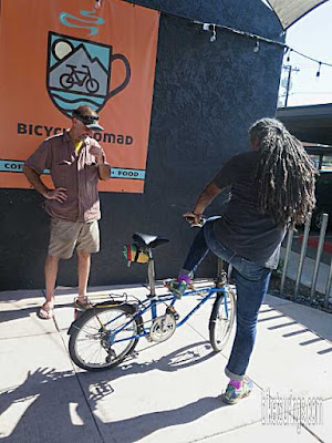 Picture of Bicycle Nomad Cafe owner Erick Cedeno test riding Dahon Mariner folding bike