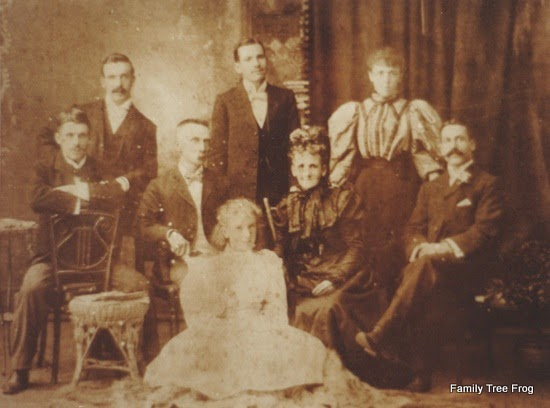 A Family Group photo - an older couple in the middle surrounded by three sons on the left and a daughter and a son on the right with a daughter seated at their feet.