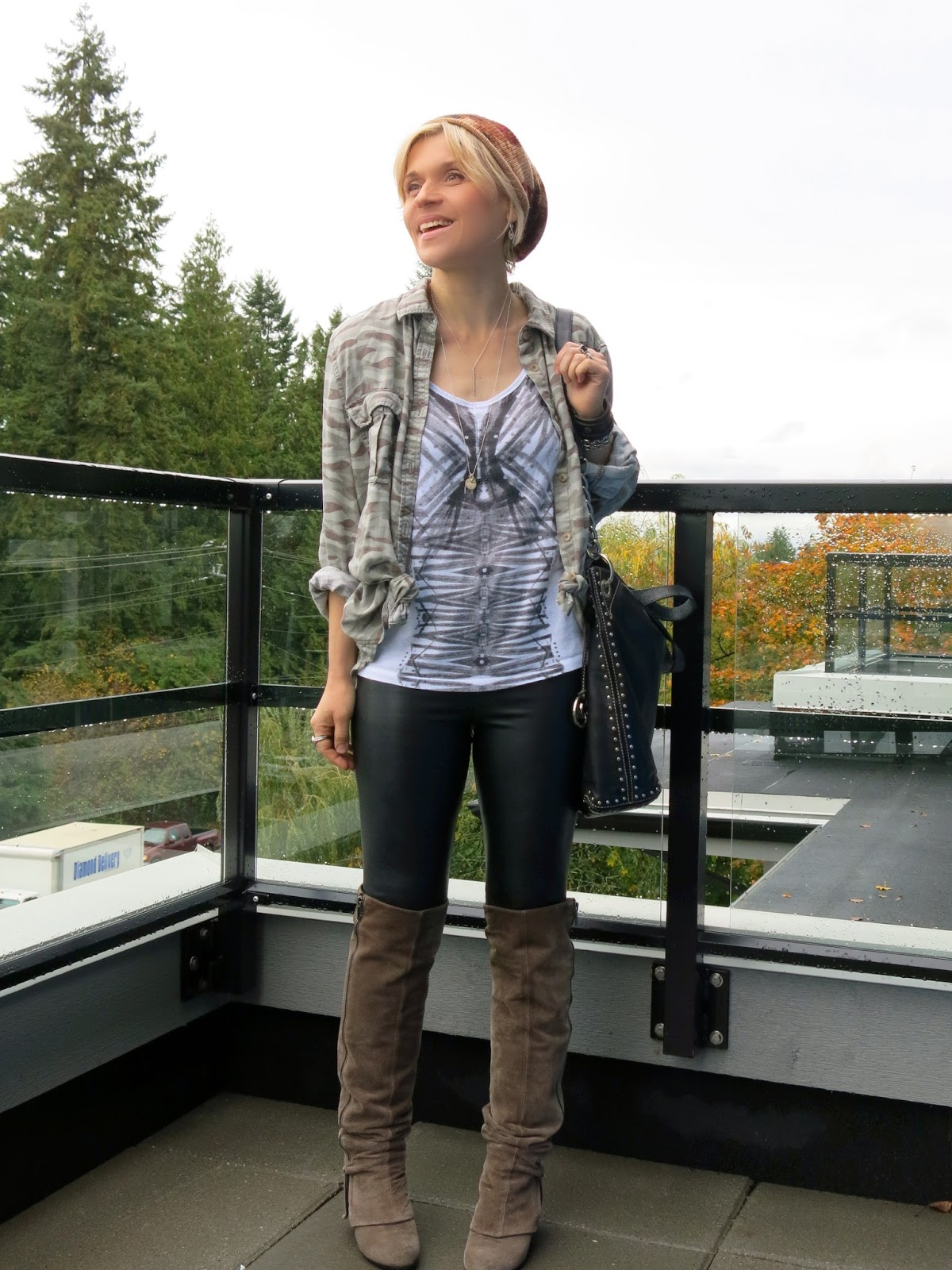 styling vegan leather leggings with over-knee suede boots, a graphic tee, camo shirt, and floral beanie