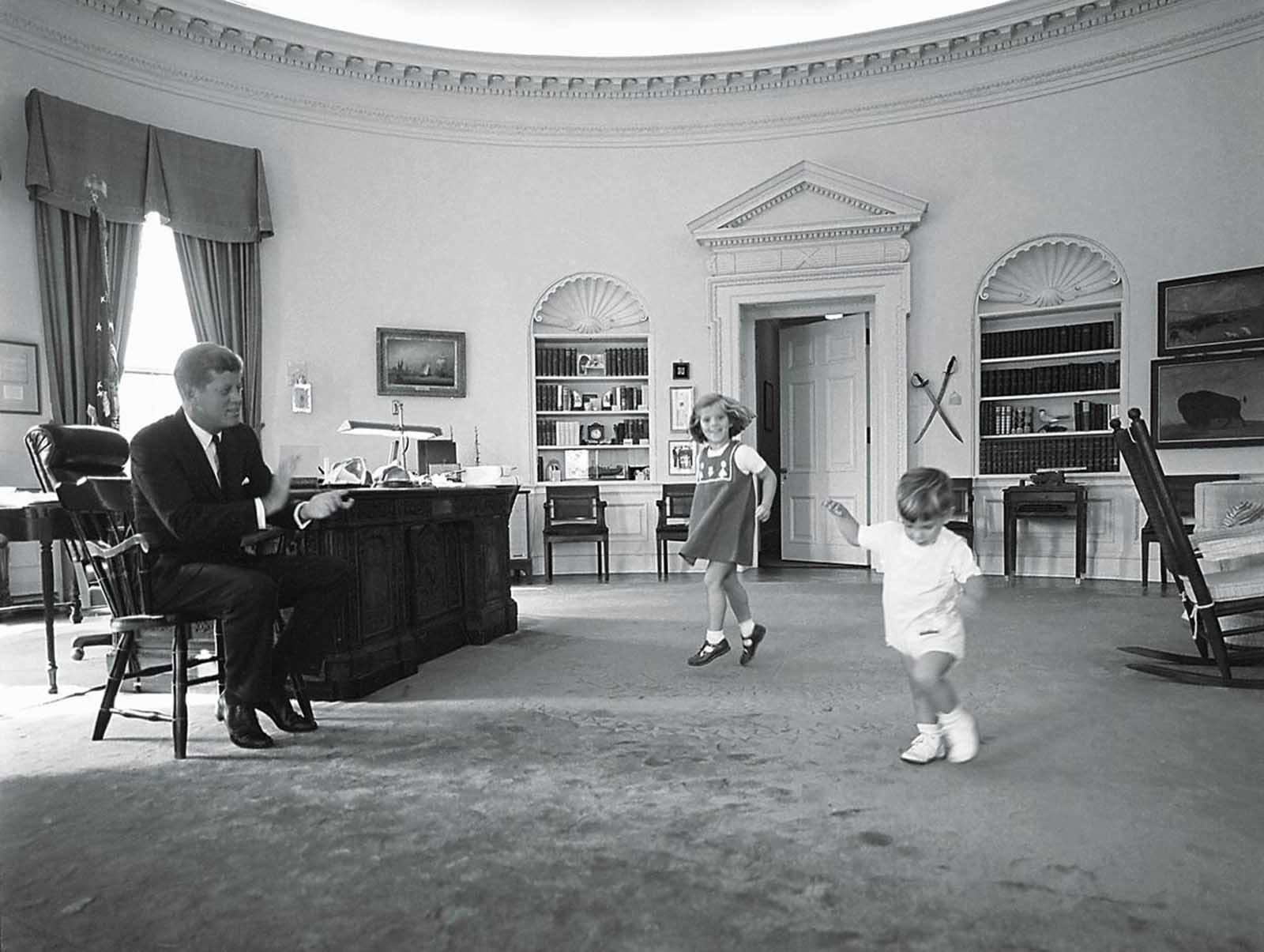 President Kennedy claps to keep time as his children Caroline and John, Jr. dance in the Oval Office, in October of 1962.