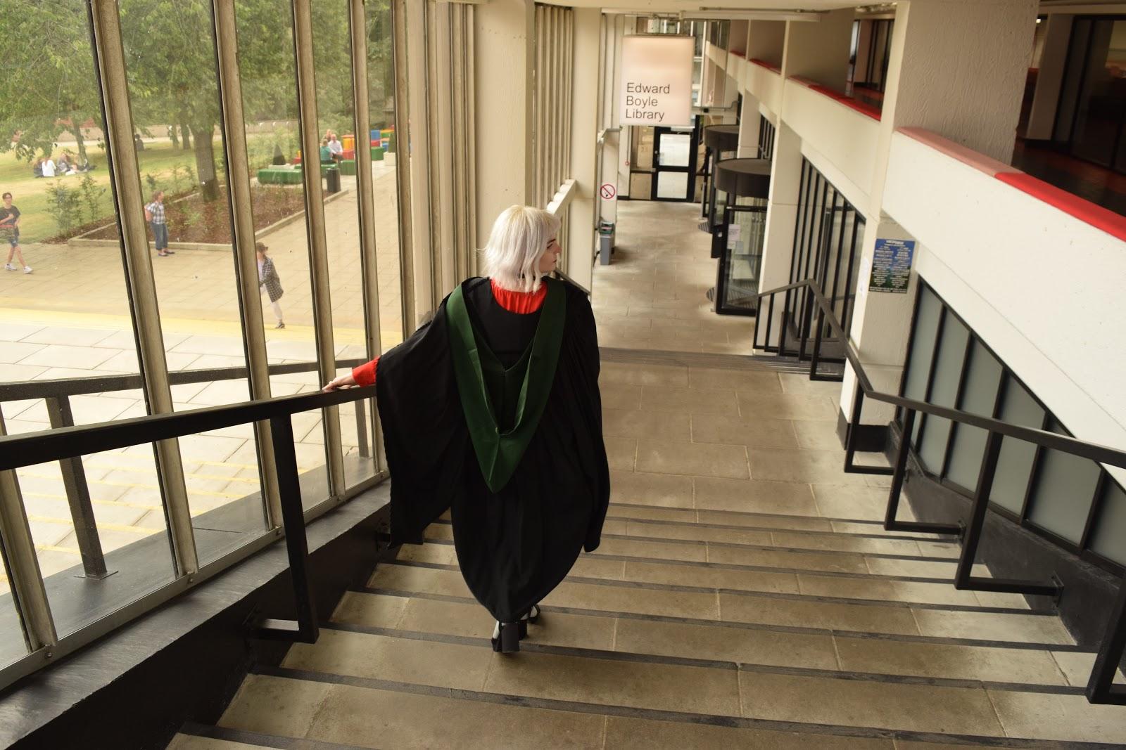 Leeds graduate in gown outside Edward Boyle Library