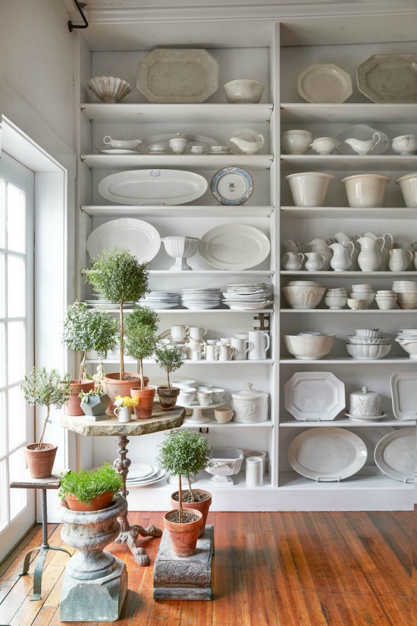 The charm of vertical built-in shelves in a vintage style kitchen is hard to beat! Ironstone, white dishware, and stoneware look elegant massed in this country style space with #shabbychic appeal. #ironstone #whitedecor #farmhousestyle