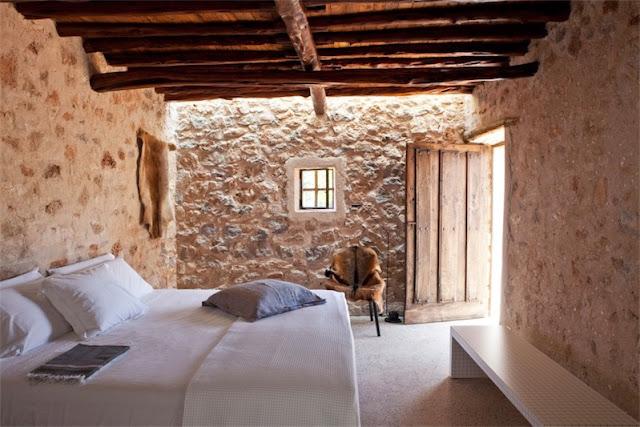 dormtiorio con paredes de piedra finca en ibiza chicanddeco